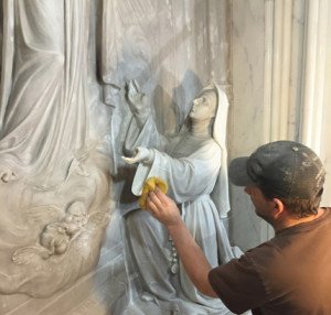 A worker shining a sacred sculpture