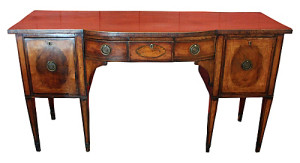 A Thomas Sheraton cherry desk with a brass gallery along its top drawers.