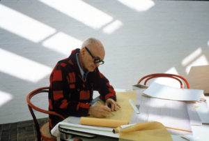 Portrait of American architect Philip Johnson (1906 - 2005) works on blueprints at a table in his office, New York, New York, 1979.