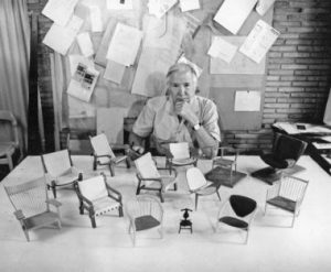 Hans Wegner with several miniatures of some of his famous wooden chairs.