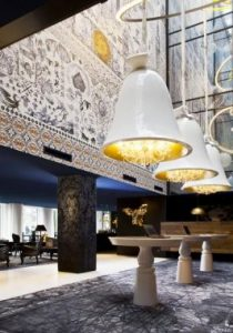 The Andaz Amsterdam Prinsengracht by Wanders. The bell-shaped chandeliers hang just below the installation, illuminating a row of reception desks, while a collection of Dutch ornaments and curiosities are displayed on a bookcase behind.