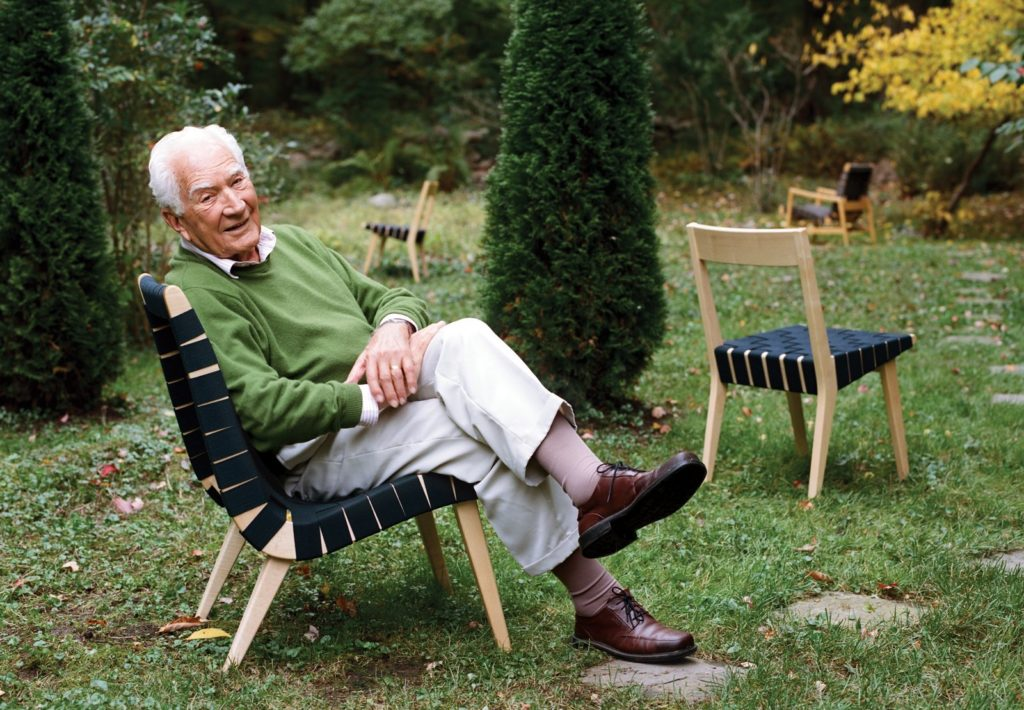 Jens Risom in his garden, with some of the chairs he designed.