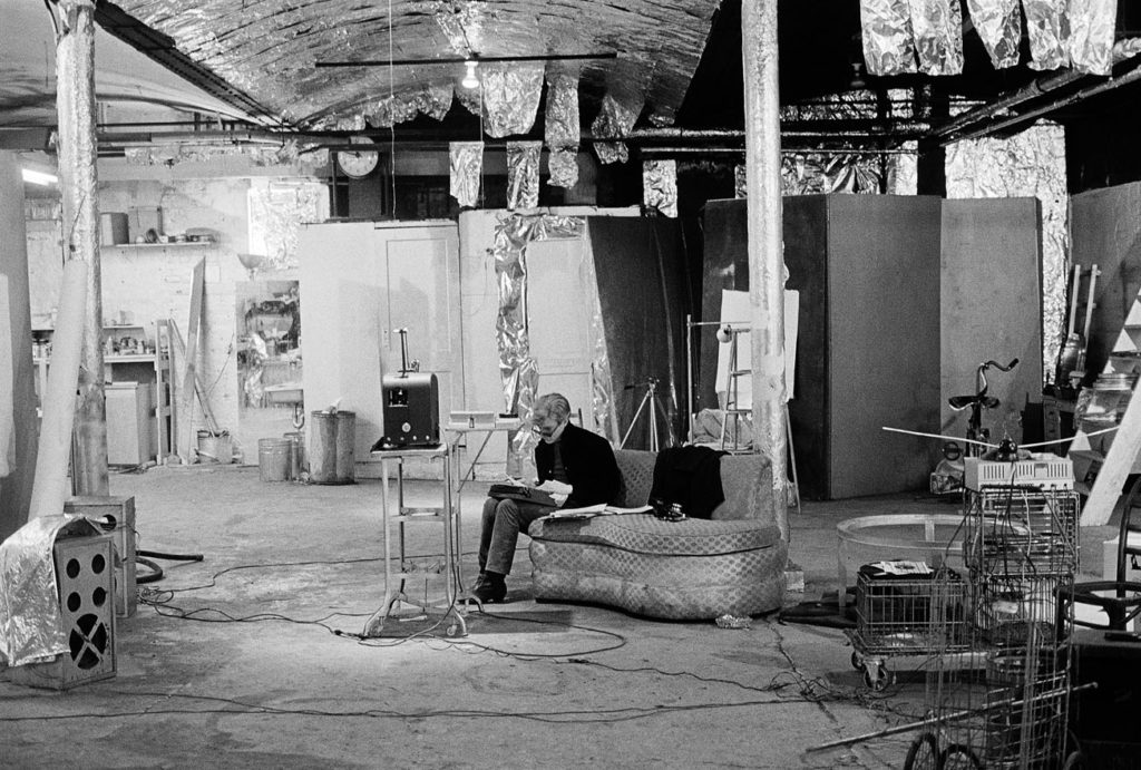 "Andy Warhol seated in ""The Factory"". Photograph by Nat Finkelstein."
